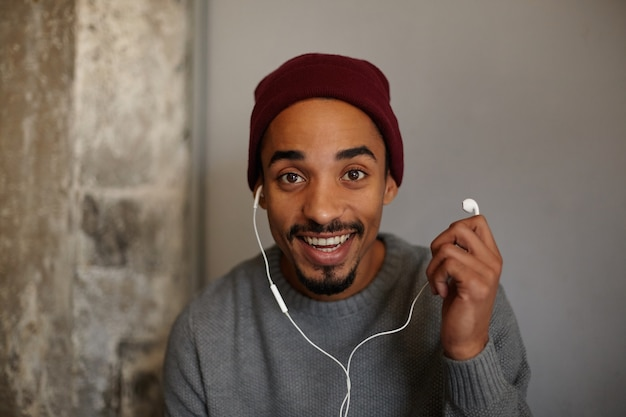 Joyful lovely young bearded man with dark skin looking with charming smile, holding earpiece and and being surprised, wearing grey sweater and burgundy headdress