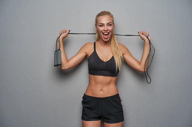 Joyful lovely young sporty blonde female with ponytail hairstyle keeping jump rope in raised hands and looking happily to camera with wide mouth opened, isolated over light grey background