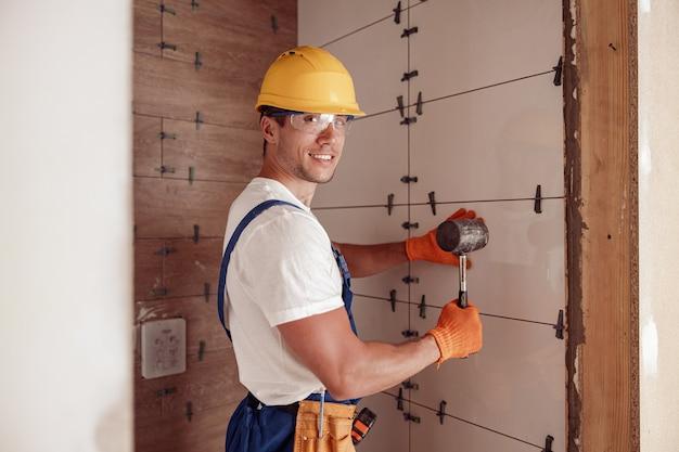 Радостный строитель-мужчина устанавливает керамическую плитку в доме