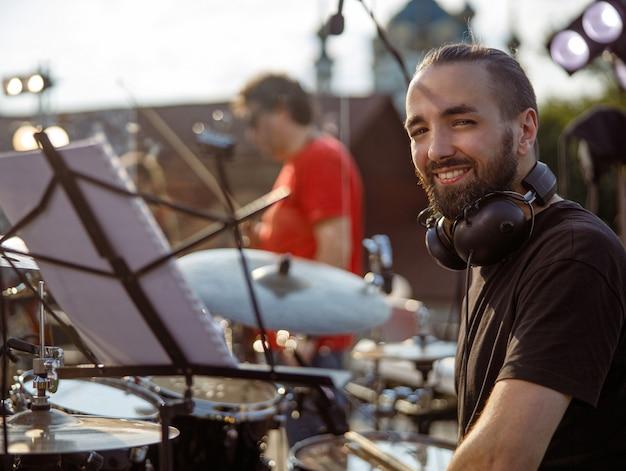 Joyful male drummer sitting at drum kit on the street