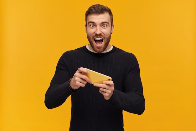 ブルネットの髪とあごひげを持つうれしそうな男性、ハンサムな男。ピアスあり。黒のセーターを着ています。黄色い壁に隔離された彼のスマートフォンでビデオゲームをプレイ