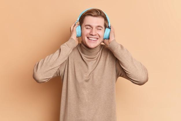 Gioioso adolescente maschio rilassato con una grande canzone indossa cuffie blu stereo sulle orecchie ha un ampio sorriso e vuole ballare vestito con un dolcevita casual