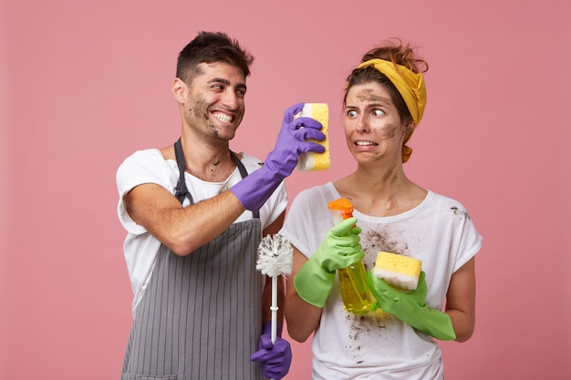 Joyful male wearing apron and protective gloves showing his wife dirty sponge very closely to her face presenting results of his work. dirty housemaid looking at dirty sponge with disgust or aversion
