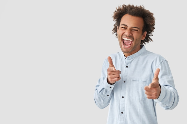 幸せな表情をしたうれしそうな男性、口を大きく開け、巻き毛があり、両方の人差し指で示し、壁の上の白いシャツのポーズに身を包んだ選択をします、空白スペース