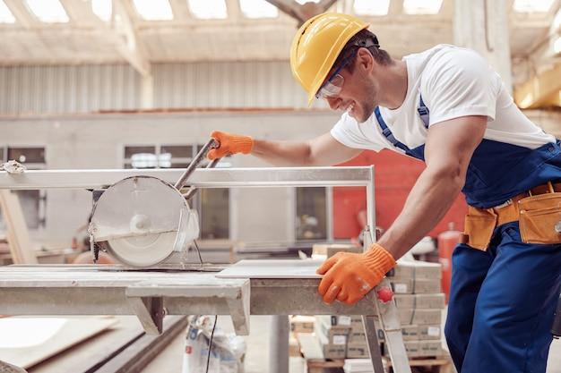 작업장에서 톱질 기계를 사용하는 즐거운 남성 노동자 프리미엄 사진