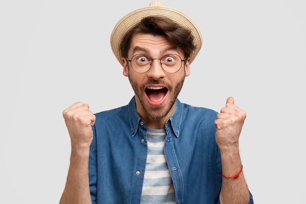 うれしそうな男の農学者は拳を食いしばり、口を大きく開き、幸せで叫び、白い壁に隔離された麦わら帽子とカジュアルなデニムシャツを着ています