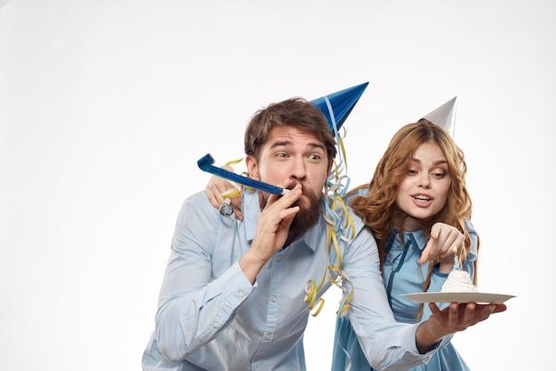 うれしそうな男と元気な女ホリデーケーキバースデーキャップパーティー企業パーティー若者。高品質の写真