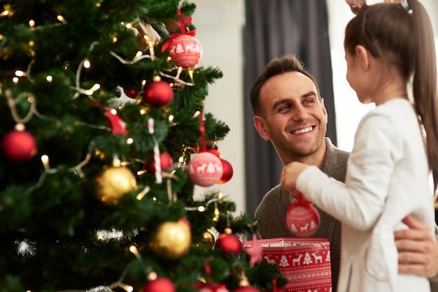 즐거운 남자와 그의 작은 딸이 크리스마스 트리 장식