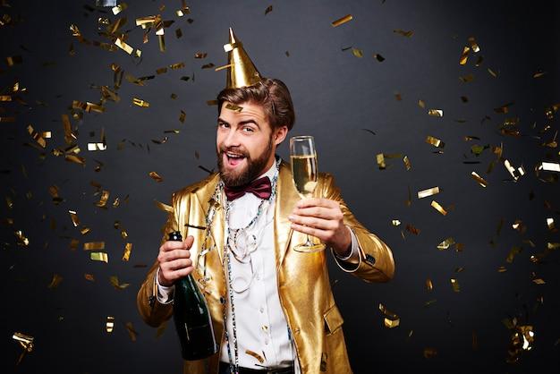 Uomo allegro che beve uno champagne