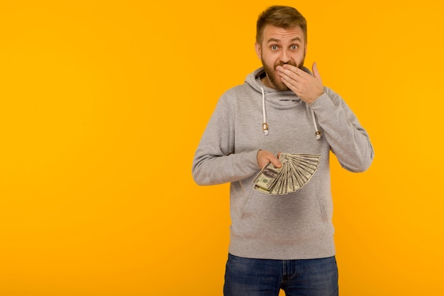 Joyful man in a gray hoodie holds money dollars covering his mouth with his hand on a yellow background - image