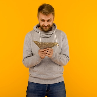 Joyful man in a gray hoodie looks at money dollars on a yellow background