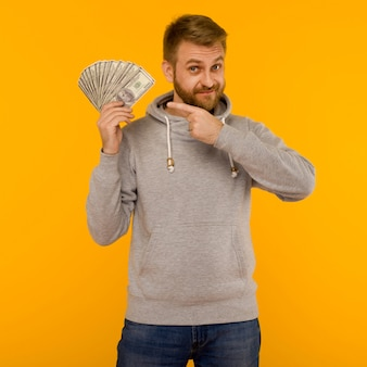 Joyful man in a gray hoodie points a finger at money dollars on a yellow background - image