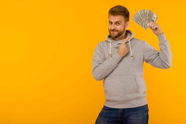 Joyful man in a gray hoodie points a finger at money dollars on a yellow background