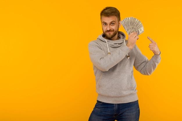灰色のパーカーのうれしそうな男は、黄色の背景にお金のドルに指を指しています