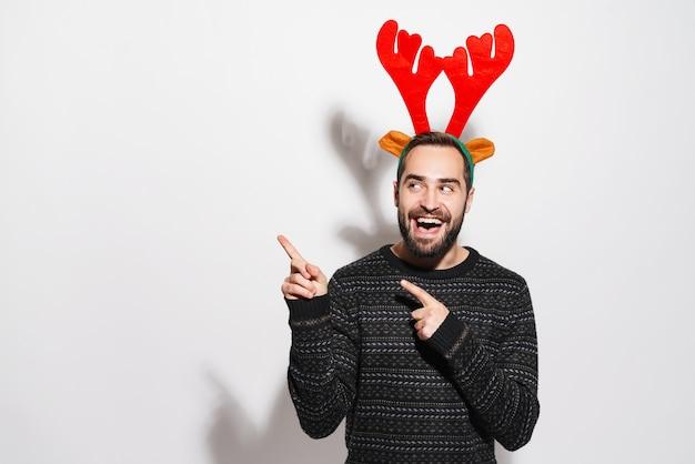 Радостный мужчина в рождественской повязке с рогами северного оленя улыбается и показывает пальцами в сторону, изолированную над белой стеной