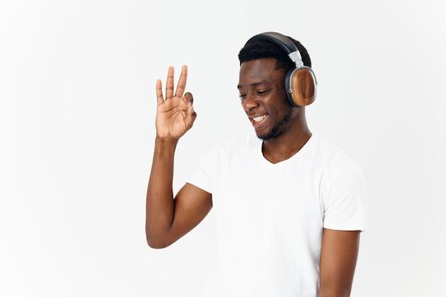 ハンドミュージック愛好家の孤立した背景で身振りで示すヘッドフォンでうれしそうな男
