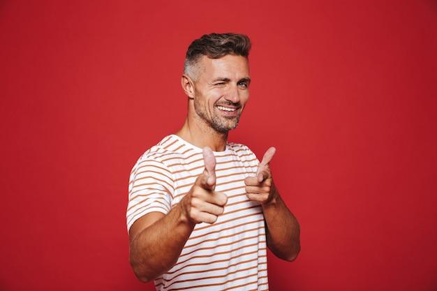 Радостный мужчина в полосатой футболке показывает указательным пальцем, что означает: