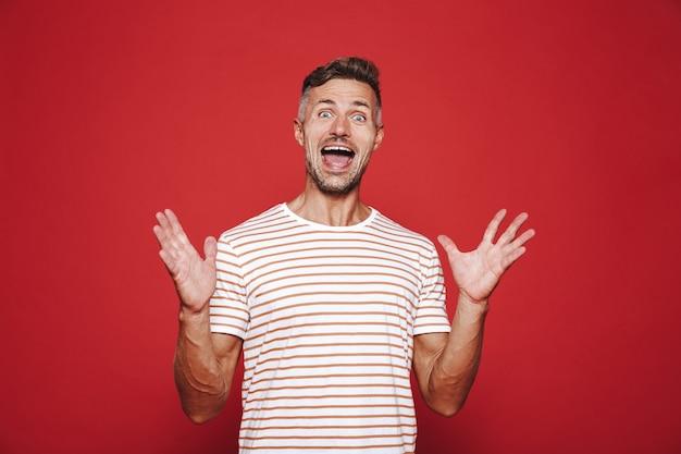 Радостный мужчина в полосатой футболке смеется и поднимает руки, изолированные на красном