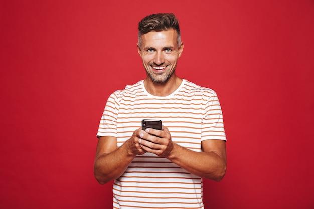 赤で隔離の携帯電話を笑顔で保持している縞模様のtシャツのうれしそうな男