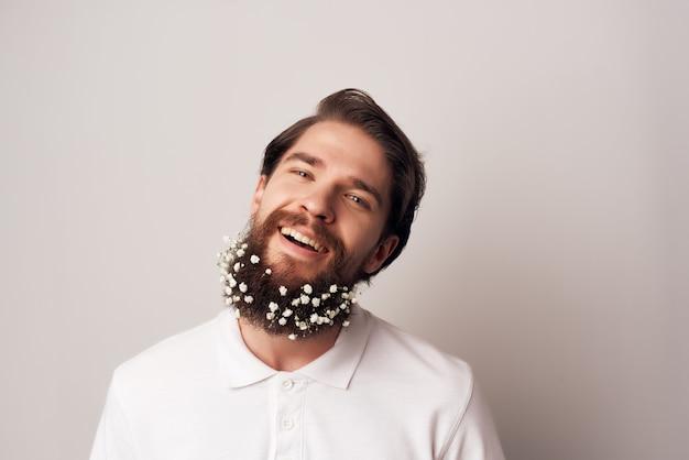 Радостный мужчина в белой футболке с цветами в украшении бородой обрезанный вид
