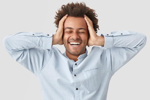 Joyful man keeps hands on head from happiness, closes eyes and smiles broadly with pleasure