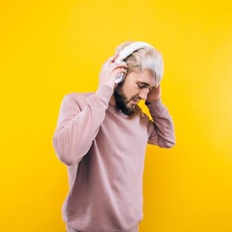 노란색 배경에 헤드폰에서 음악을 듣고 즐거운 남자