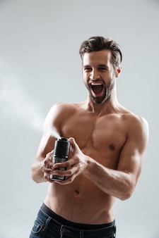 Joyful man playing with deodorant