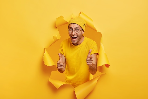 Uomo allegro che posa attraverso carta strappata