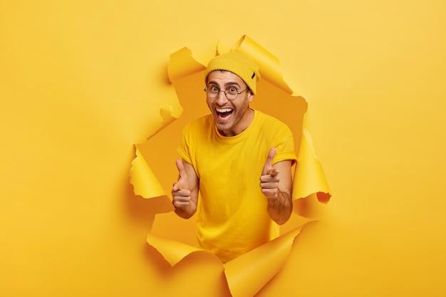 Joyful man posing through torn paper