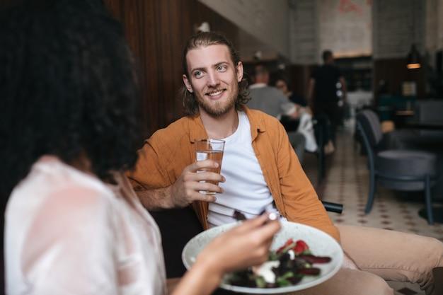 레스토랑에 앉아 여자와 이야기하는 즐거운 남자