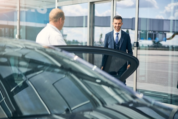 車の横に立っているタクシー運転手に会って空港を出て微笑んでうれしそうな男