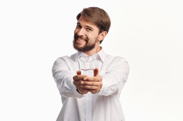 Радостный мужчина протягивает руку со стаканом воды вперед на светлой стене.
