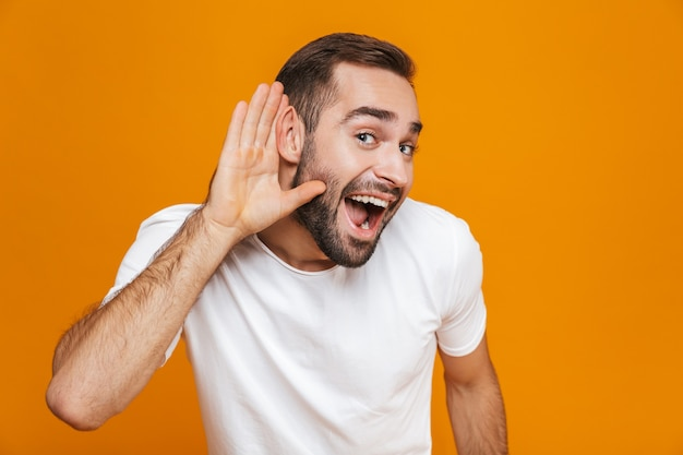 Joyful man trying to hear something while keeping hand at his ear, isolated on yellow