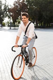 도시 거리에서 자전거를 타고 공식적인 옷을 입고 즐거운 남자