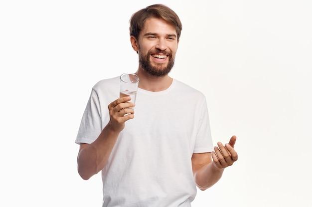 Радостный человек со стаканом воды белая футболка светлом фоне.