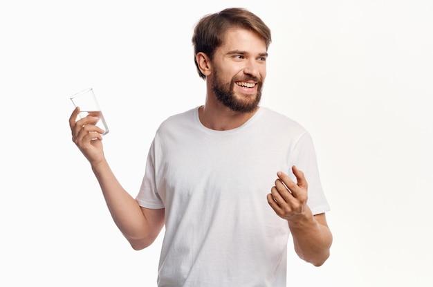Радостный мужчина со стаканом воды, белая футболка, легкий образ жизни, жестикулирующий руками