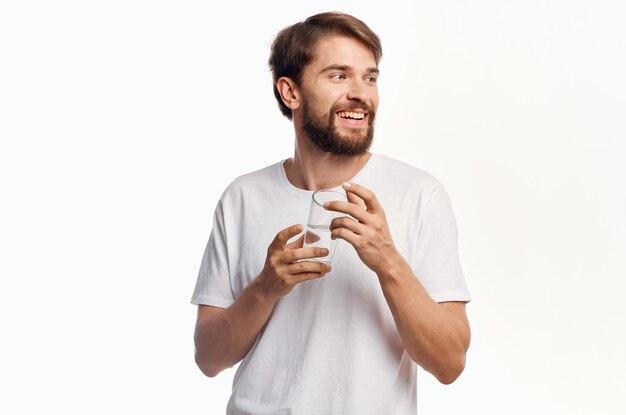 Радостный мужчина со стаканом воды белая футболка светлая