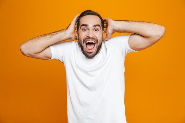 Радостный мужчина с бородой и усами хватается за голову стоя, изолированный на желтом