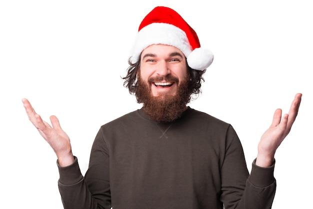 Радостный мужчина с бородой в шляпе санта-клауса и делает приветственный жест
