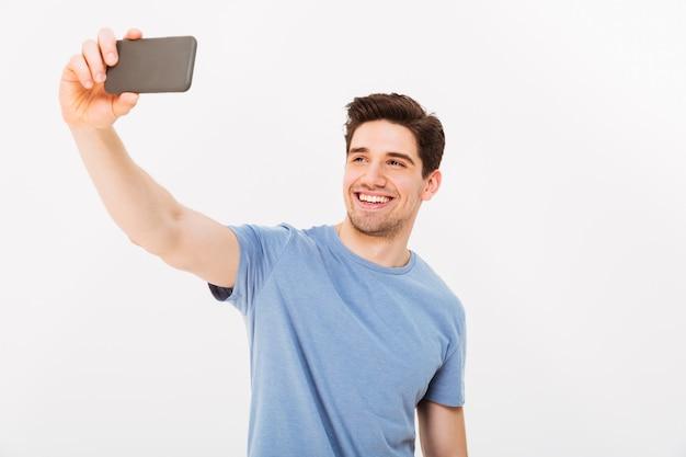 Радостный человек с каштановыми волосами, улыбаясь в камеру, принимая селфи на черном мобильном телефоне, изолированном над белой стеной