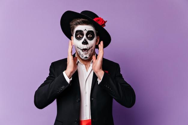 L'uomo allegro con il trucco di halloween in stato di shock esamina la macchina fotografica, in posa su sfondo viola.