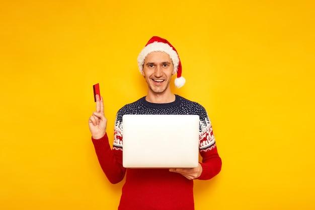 노트북을 손에 들고 즐거운 남자는 플라스틱 신용 카드로 크리스마스 선물을 산다