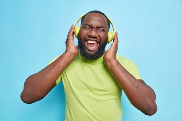 Joyful man with thick beard keeps hands on headphones laughs happily enjoys favorite music wears casual green t shirt isolated over blue wall