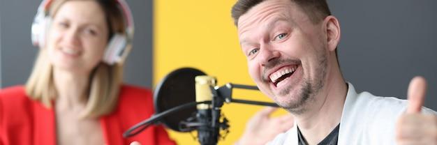 Joyful man and woman are working on air of radio station profession training radio host concept