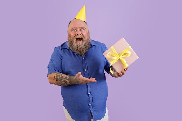 黄色のパーティーハットで太りすぎのうれしそうな成熟したひげを生やした男は、スタジオで紫色の背景にポーズをとって弓とギフトボックスを保持します。