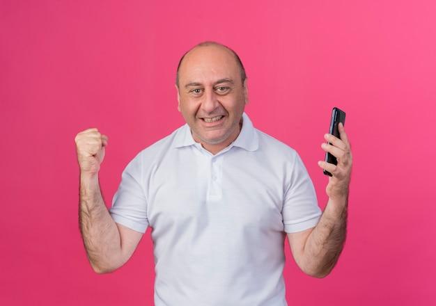 Радостный зрелый бизнесмен держит мобильный телефон сжимая кулак делает жест да