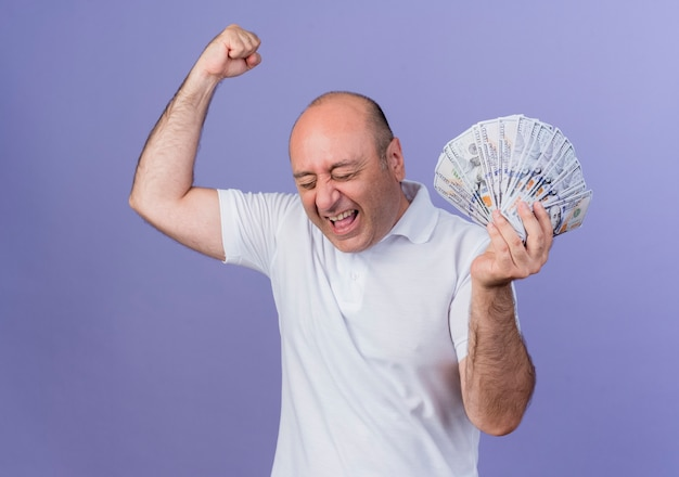Joyful mature businessman holding money raising fist doing yes gesture with closed eyes