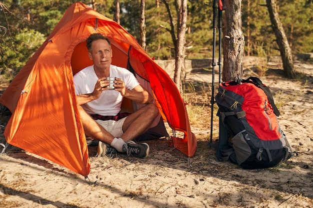 Joyful mature male is relaxing with cup of hot drink after nordic walking in sunny forest