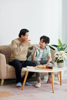 Joyful mature man enjoying spending weekend with son at home, they are drinking tea, eating potato chips and discussing news