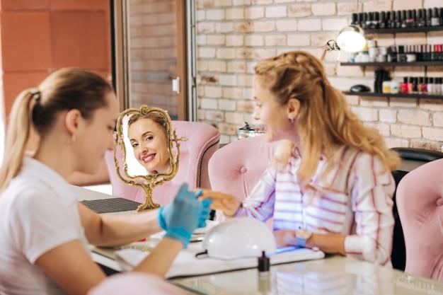 Радостная зрелая женщина лечит ногти под уф-лампой и улыбается в зеркало